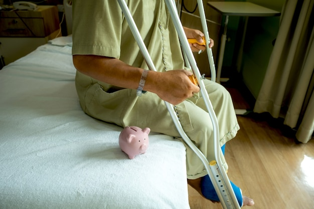 A piggy bank with a man's leg uses crutches to walk after surgery recovery injury broken bones.
