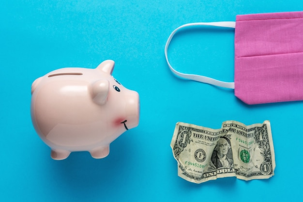 Piggy bank with a medical face mask and crumpled dollar bancnote