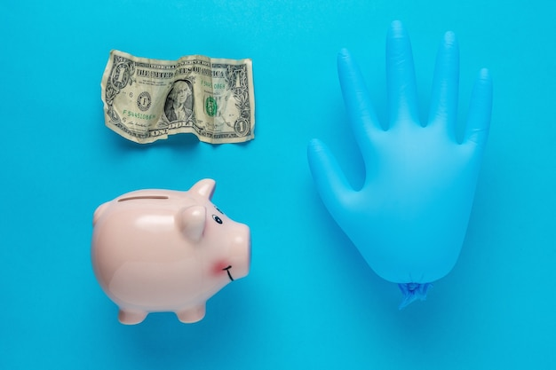 Piggy bank with a medical glove and crumpled dollar bancnote