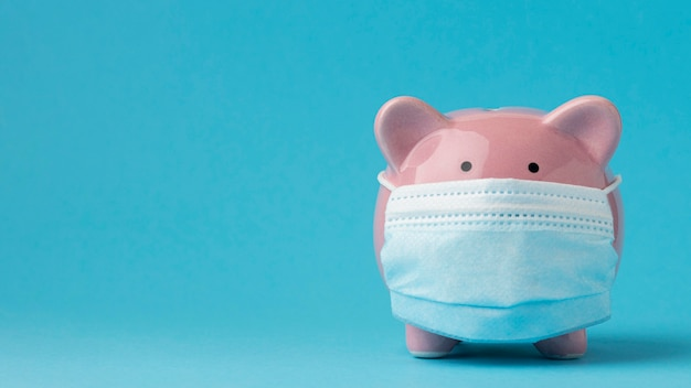 Piggy bank with medical mask and copy space