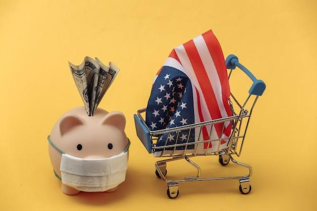 의료용 마스크가 있는 돼지 저금통, 노란색 배경에 미국 국기가 달린 미니 슈퍼마켓 트롤리
