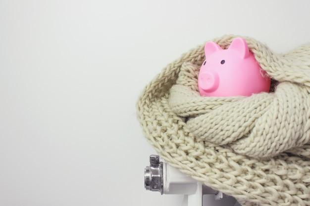 Копилка с деньгами и шарфом на радиаторе. понятие отопительного сезона.