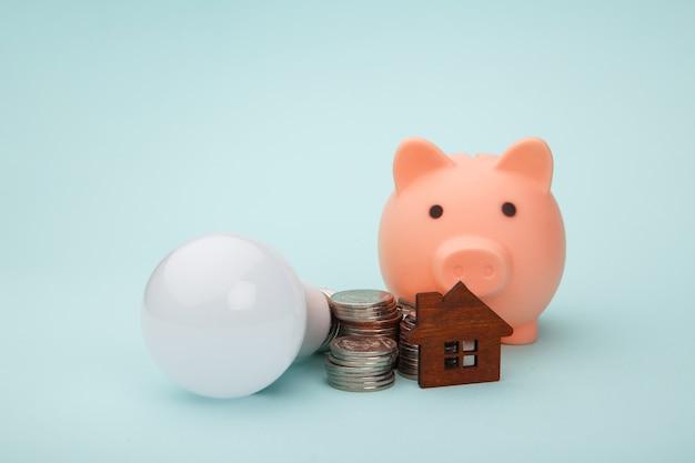 Копилка с денежной банкнотой и светодиодной лампочкой, дом рисунок на синем фоне. концепция энергосбережения