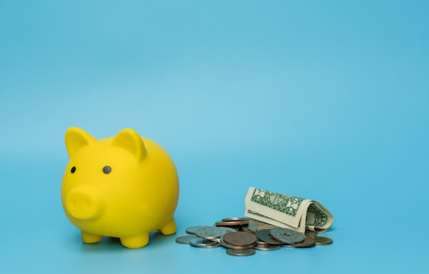 青い背景にお金の貯金箱。お金を節約するコンセプト