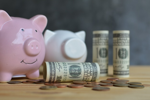 Piggy bank with money on wood table saving concept.
