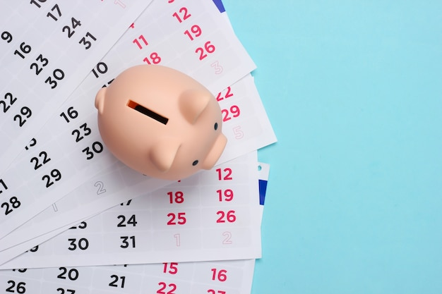 Piggy bank with a monthly calendar on a blue
