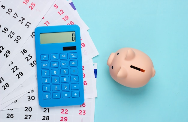 Piggy bank with a monthly calendar, calculator on a blue. payment of rental housing or loans