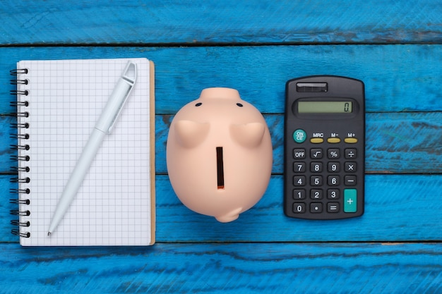 Piggy bank with notebook and calculator on a blue wooden surface. top view