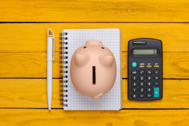 Piggy bank with notebook and calculator on a yellow wooden surface. top view