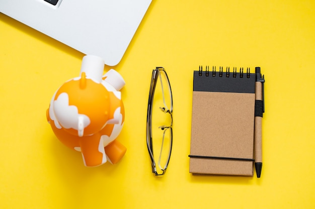 Piggy bank with notepad and computer on yellow background