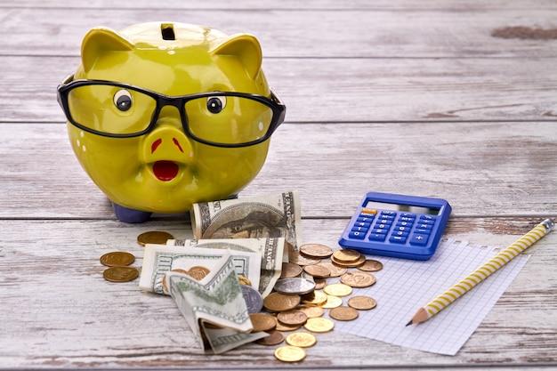 Копилка с кучей долларов, монет, калькулятора, чистого листа бумаги и карандаша