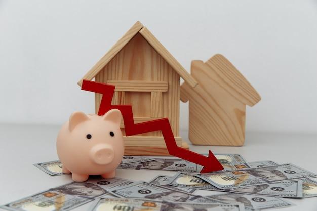 빨간색 화살표 아래로 돼지 저금통과 달러 돈 절약 또는 구매 집 또는 부동산 개념에 대한 대출에 목조 주택 모델