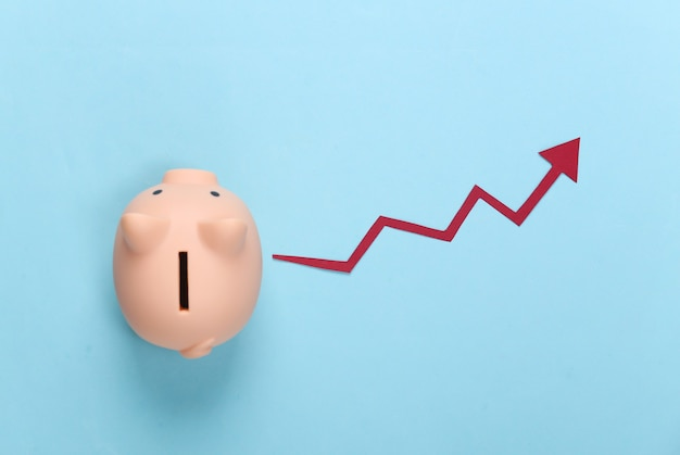 Piggy bank with red growth arrow on blue. arrow graph going up. the economic growth