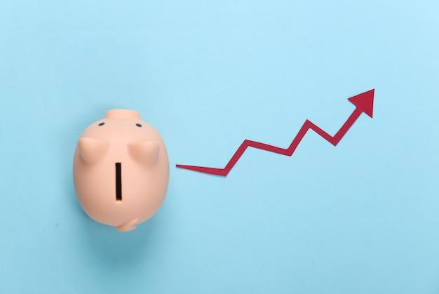 파란색에 빨간색 성장 화살표와 함께 돼지 저금통입니다. 올라가는 화살표 그래프. 경제 성장