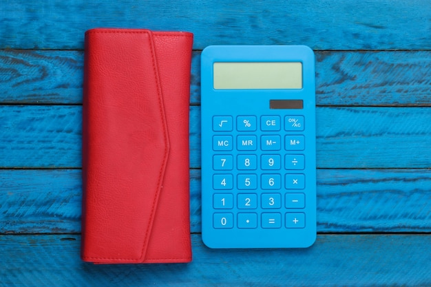 Piggy bank with red leather wallet on a blue wooden surface. top view