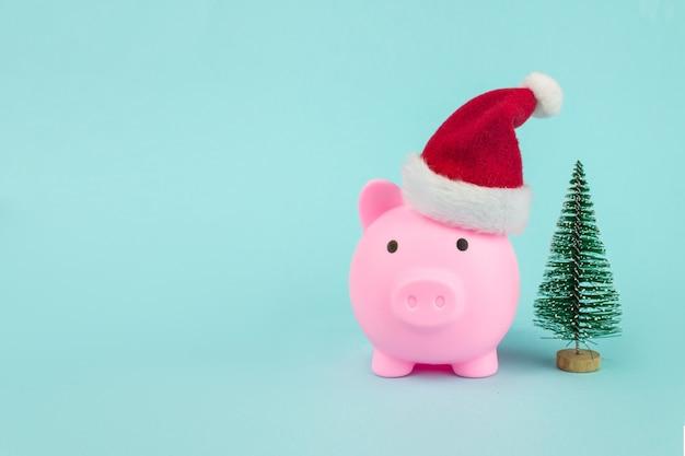 파란색 배경에 christmass 나무와 산타 모자와 돼지 저금통. 새 해의 상징입니다.