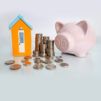 Piggy bank with small house and coin on white background