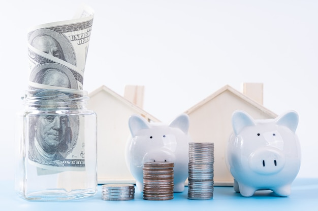 스택 동전과 항아리와 목조 주택 절연 회색 배경 안에 돈 종이 돼지 저금통. 부동산 투자 및 주택 모기지 금융 개념.