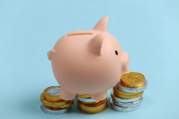 파랑에 동전의 스택과 함께 돼지 저금통입니다.