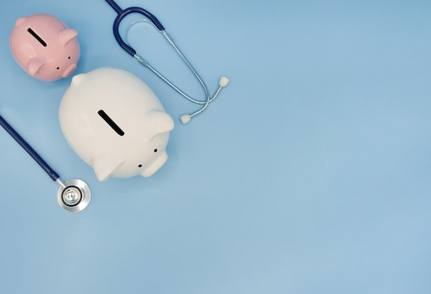 Piggy bank with stethoscope on blue health care financial checkup saving medical insurance concept