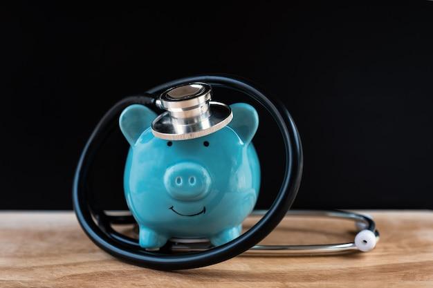 청진기가 있는 돼지 저금통은 정기적으로 건강 저축 개념을 확인합니다.
