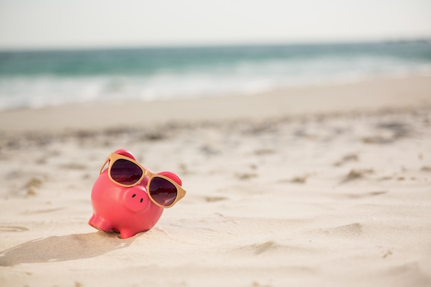 Piggy bank with sunglasses kept on sand
