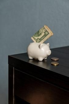 우리와 함께 돼지 저금통 달러와 동전 테이블에. 돈 개념을 저장합니다.