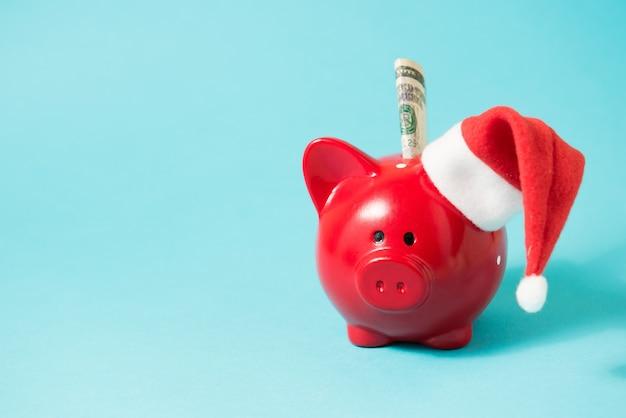 파란색 배경에 1달러 지폐와 산타클로스 모자가 있는 돼지 저금통