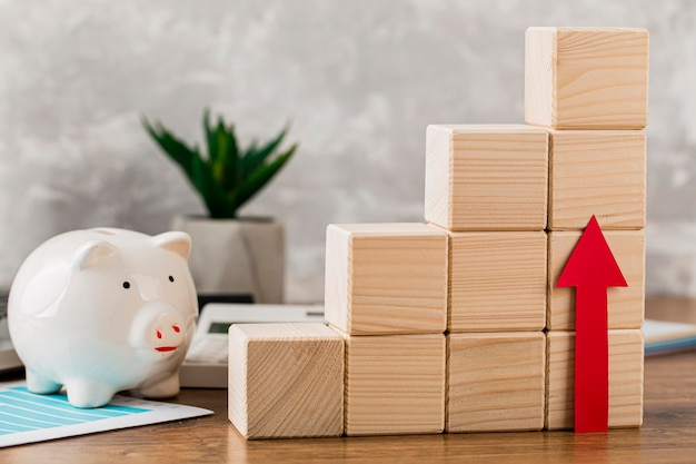 Piggy bank with wooden growth blocks and arrow pointing up