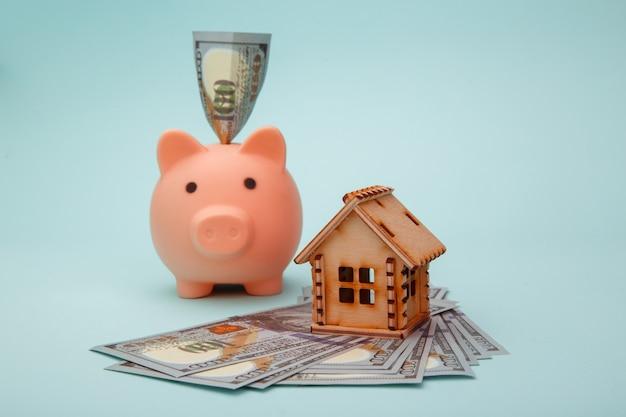青の家とお金の紙幣の木製モデルと貯金箱