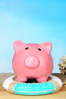 Piggy bank on wooden table, outdoors