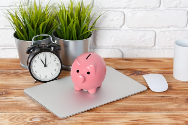 Piggy money box with laptop on wooden table