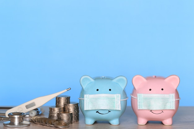 Piggy with wearing protective medical mask and thermometer with stack of coins money on wooden background, save money for medical insurance and health care concept