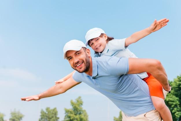 ピギーバックライド。屋外に立っている間彼の息子をピギーバックする笑顔の若い男