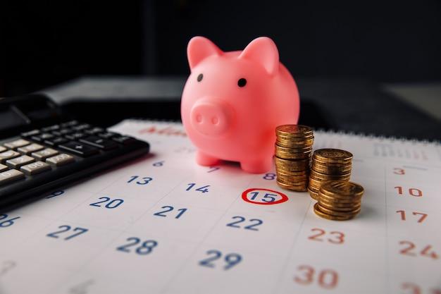 Piggybankとカレンダー上のコインのスタック