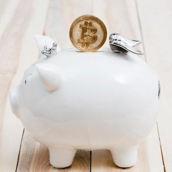 木製のテーブル上の白いpiggybankのスロットの上にゴールデンbitcoins