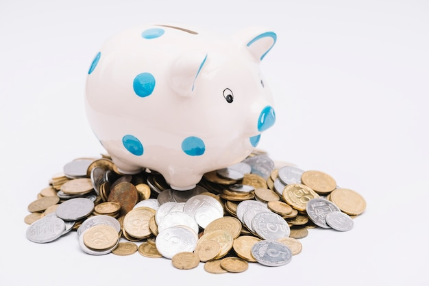Piggybank over many coins on white background Free Photo