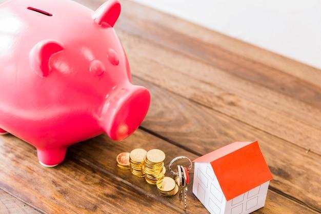 Piggybank、積み重ねられたコイン、家そして木製の机の上のキー