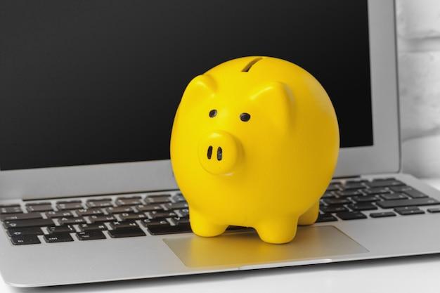 お金を節約の概念でノートパソコンのキーボードのpiggybank