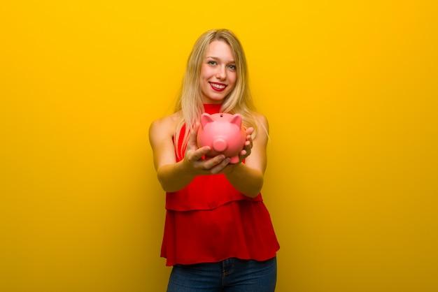 Piggybankを保持している黄色の壁の上の赤いドレスの少女