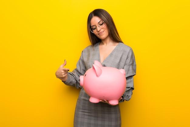 Piggybankを保持している黄色の壁の上の眼鏡の若い女性
