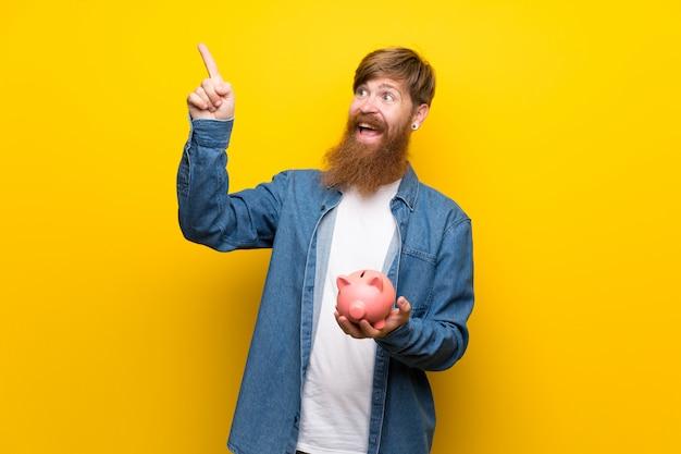 大きなpiggybankを保持している孤立した黄色の壁の上の長いひげを持つ赤毛の男