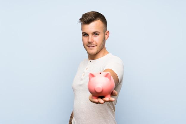 大きなpiggybankを保持している分離の青い壁の上の若いハンサムな金髪男
