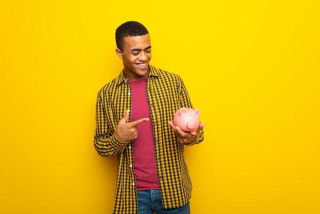 Piggybankを保持している黄色の壁に若いアフロアメリカン男
