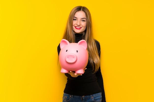 Молодая милая женщина над желтой стеной держа piggybank