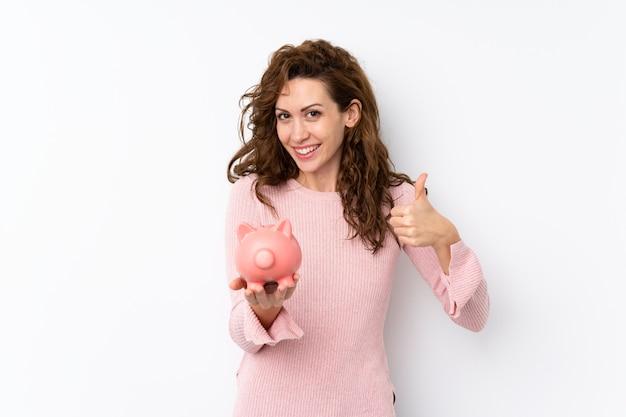 Молодая милая женщина над изолированным держащ большой piggybank