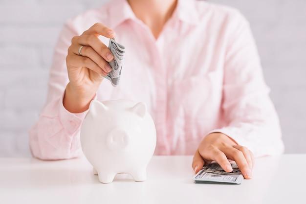 Крупным планом женщина, вставляющая стодолларовую валюту в белый piggybank