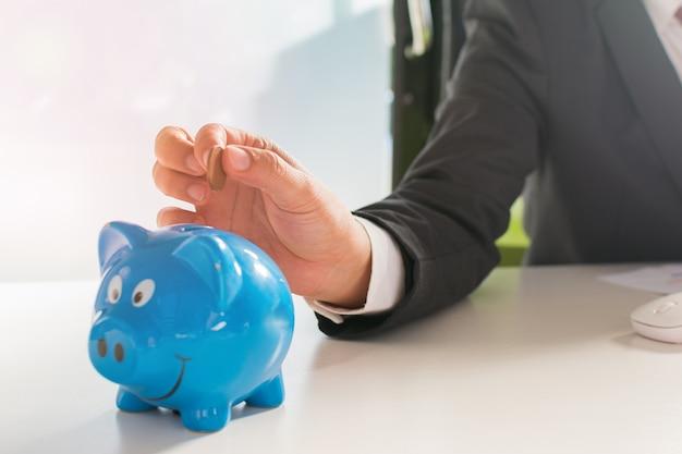 Бизнесмен, вставляющий монету в piggybank и дом модели