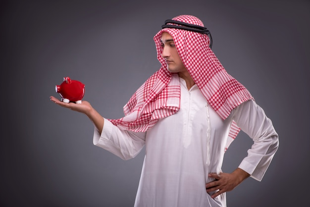 灰色のpiggybankとアラブのビジネスマン