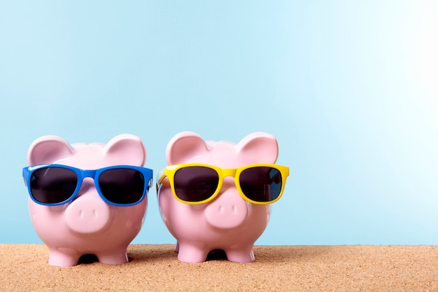 Piggybanks on a beach with sunglasses